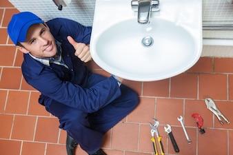 Smiling plumber repairing sink showing thumb up