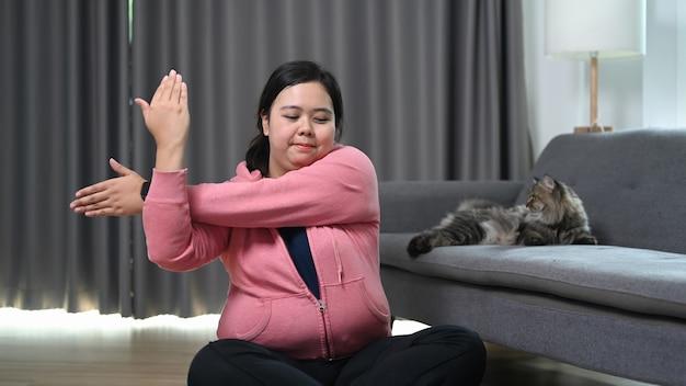 家で運動する前に腕を伸ばしているふっくらとした女性の笑顔。