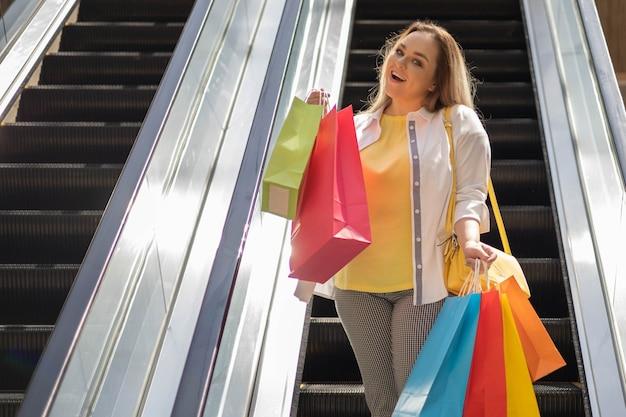 カラフルな買い物袋でエスカレーターでポーズをとって笑顔のプラスサイズの金髪の女性のバイヤー