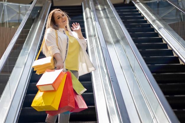 Улыбающийся покупатель блондинки больших размеров позирует на эскалаторе с красочными сумками для покупок