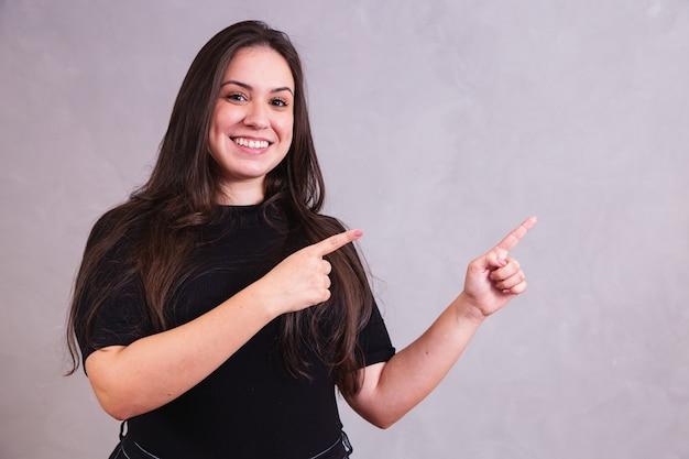 テキスト用のスペースがある側を指している笑顔のプラスサイズの女性。