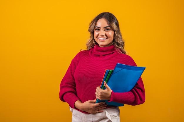 黄色の背景に手に教科書を持つ笑顔のプラスサイズの女子学生。