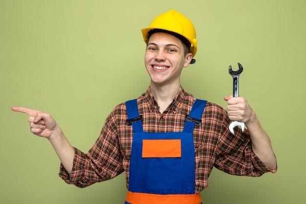 Sorridente punti sul lato giovane costruttore maschio che indossa un'uniforme che tiene una chiave aperta