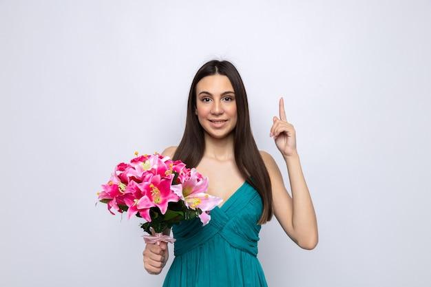 Sorridere indica la bella ragazza durante la festa della donna felice che tiene il mazzo isolato sul muro bianco con lo spazio della copia