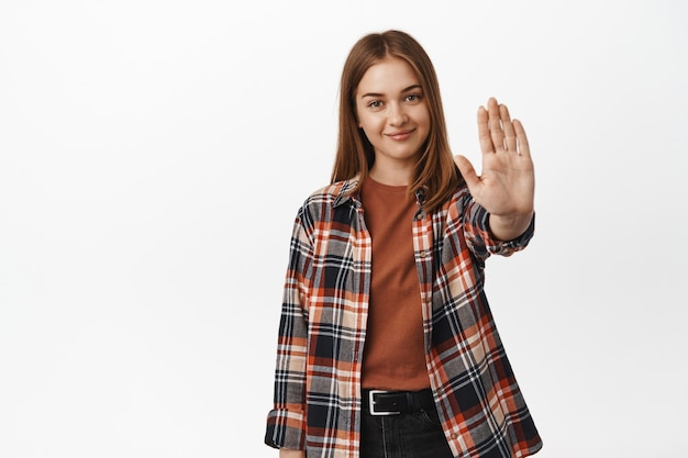 笑顔の礼儀正しい女性はノーと言い、手を伸ばしてブロックし、ジェスチャーを禁止し、遠ざかり、禁止または反対し、カジュアルな服装で白い壁に立ちます