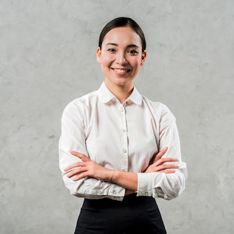 Smiling portrait of a asian young woman with her arms crossed looking to camera against grey concrete wall