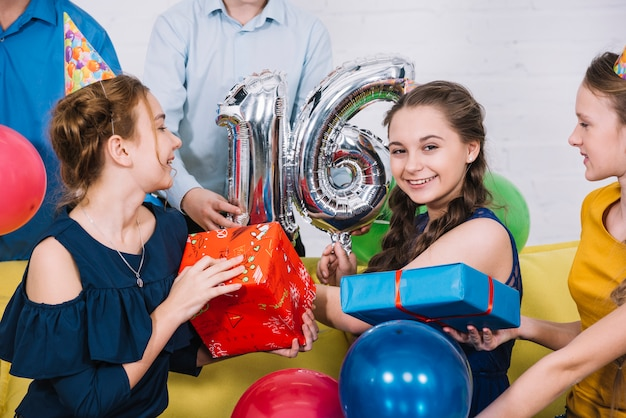 Smiling portrait of birthday girl with number 16 foil balloon and presents