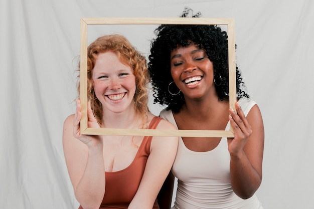 Smiling portrait of blonde and african young women holding wooden frame in front of their face