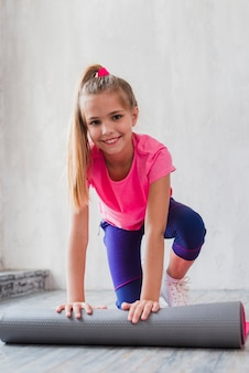 Smiling portrait of a blonde girl rolling the exercise mat in front of wall