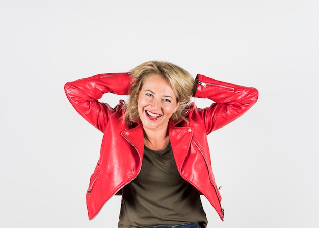 Smiling portrait of a blonde mature woman in red leather jacket standing against white background