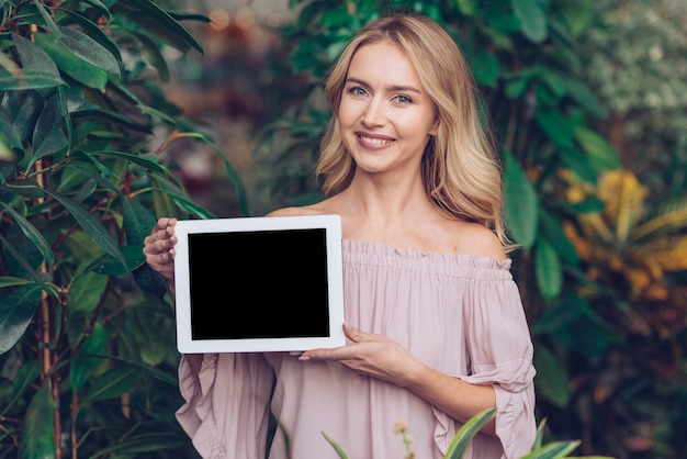 Smiling portrait of a blonde young woman showing blank display digital tablet