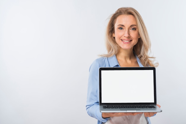 Smiling portrait of a blonde young woman showing laptop with blank display on her hand