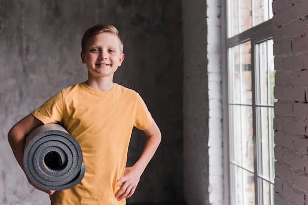 Smiling portrait of a boy holding grey rolled up exercise mat