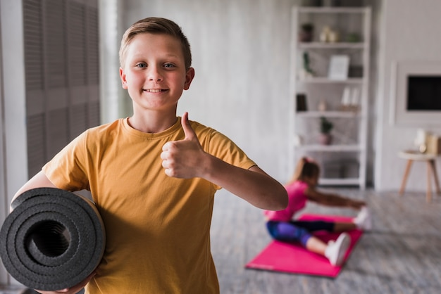 Smiling portrait of a boy holding rolled up exercise mat showing thumbs up sign