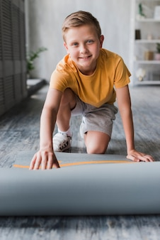 Smiling portrait of a boy placing exercise mat on floor