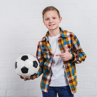 Smiling portrait of a boy showing his soccer ball standing against white brick wall