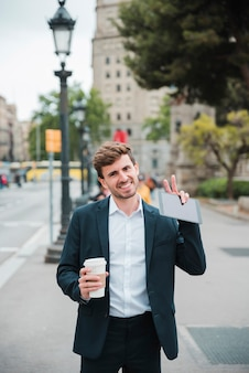 Smiling portrait of a businessman holding takeaway coffee cup and digital tablet showing victory gesture