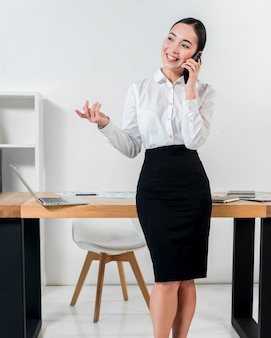 Smiling portrait of a businesswoman standing in front of desk talking on mobile phone gesturing