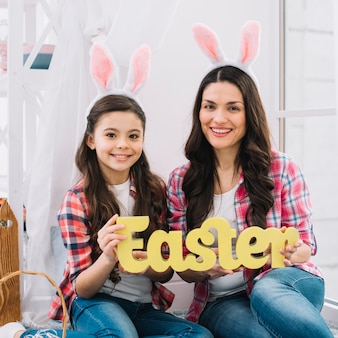Smiling portrait of a daughter and mother with bunny ears holding easter text