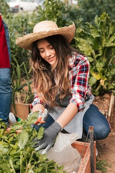 Smiling portrait of a female gardener pruning the plants
