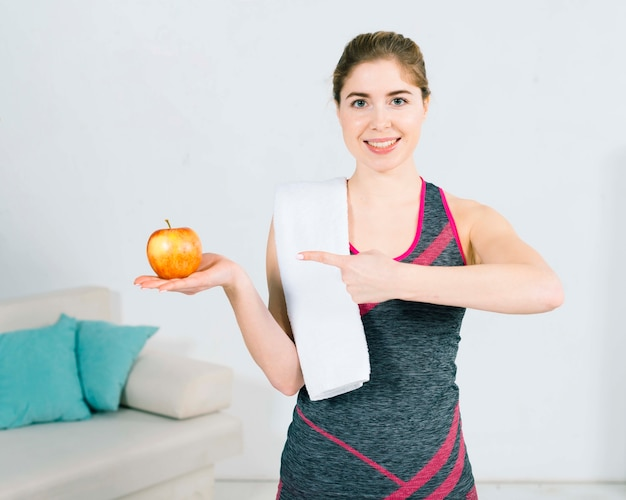Smiling portrait of fitness young woman pointing her finger toward the whole fresh apple