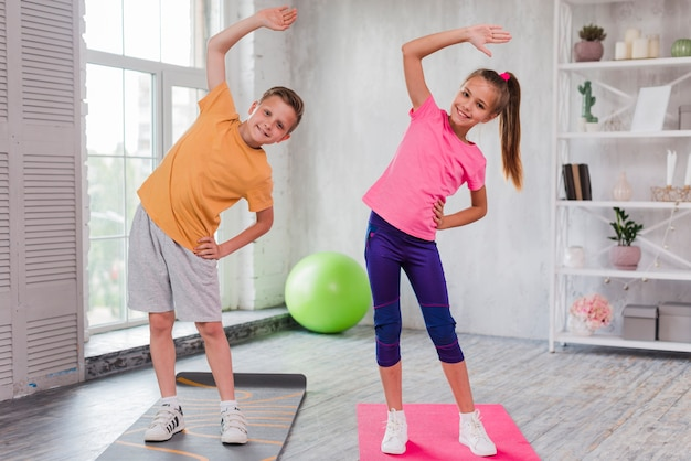 Smiling portrait of a girl and boy standing on exercise mat stretching