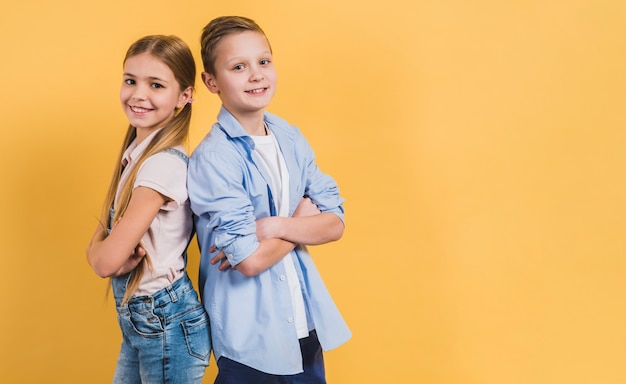Smiling portrait of a girl and boy with arm crossed standing back to back against yellow background