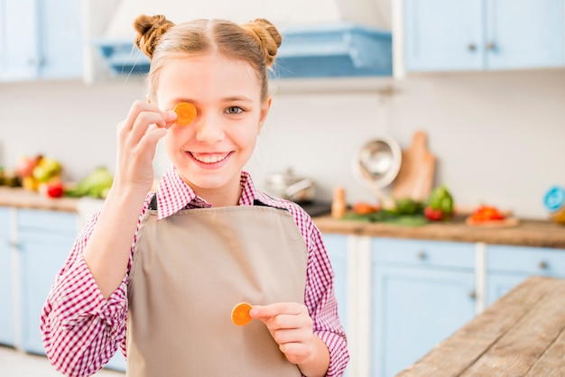 Smiling portrait of a girl covering her one eye with carrot in the kitchen