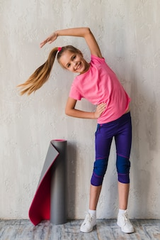 Smiling portrait of a girl doing stretching exercise in front of concrete wall