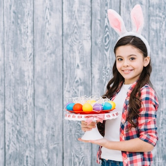 Smiling portrait of a girl holding easter eggs on cakestand looking to camera