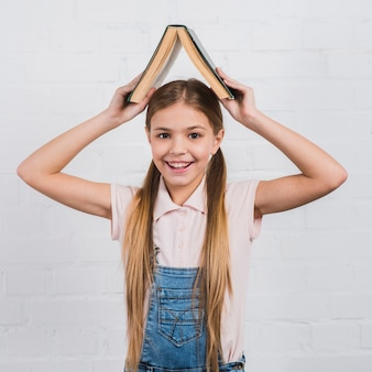 Smiling portrait of a girl holding an open book on her head looking to camera