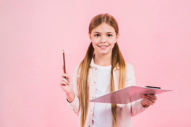 Smiling portrait of a girl holding pencil and clipboard in hands against pink backdrop