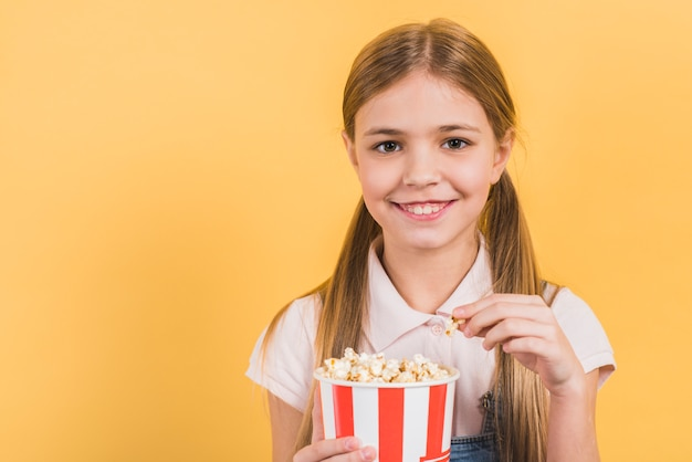 Smiling portrait of a girl holding popcorn bucket against yellow backdrop