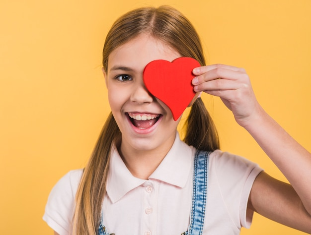 Smiling portrait of a girl holding red paper cut out heart shape in front of her eyes against yellow background