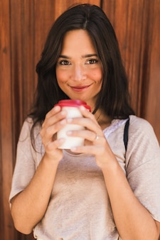 Smiling portrait of a girl holding take away coffee cup