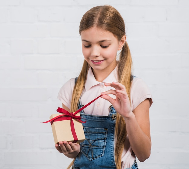 Smiling portrait of a girl opening the gift box standing against white brick wall