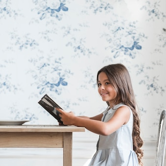 Smiling portrait of a girl reading sitting in front of wallpaper reading book