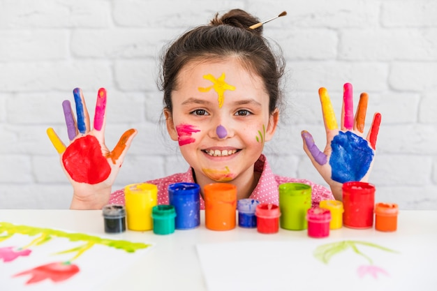 Smiling portrait of a girl behind the table with paint bottles showing her hand and face painted with colors
