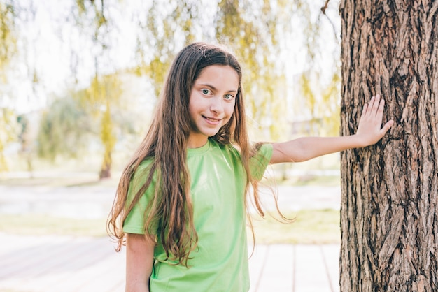 Smiling portrait of a girl touching his hand on tree trunk