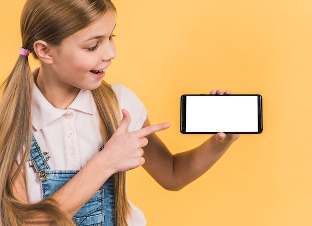 Smiling portrait of a girl with long blonde hair pointing at mobile phone showing white blank screen