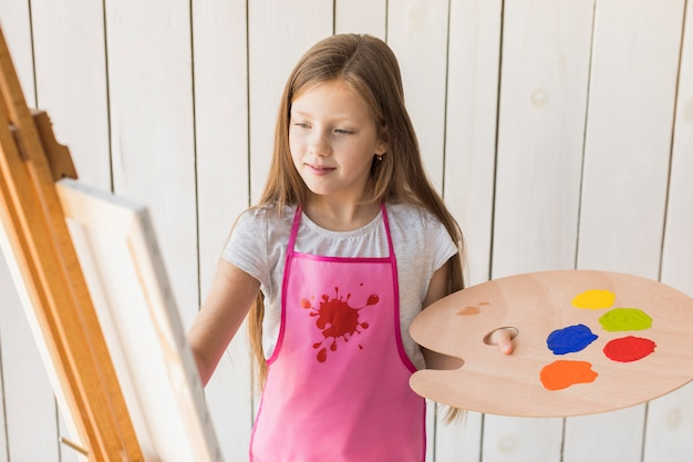Smiling portrait of a girl with pink apron painting on canvas