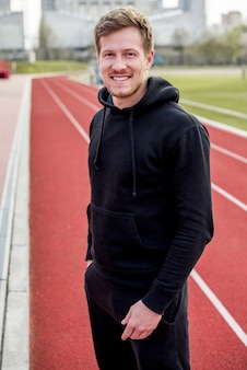Smiling portrait of a male athlete standing on race track