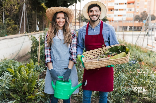 Smiling portrait of a male and female gardener holding watering can and basket in the garden