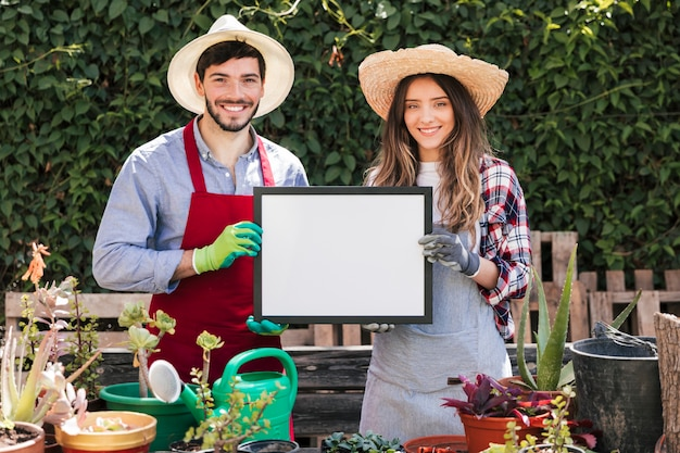 Smiling portrait of a male and female gardener wearing hat showing white blank frame in the garden