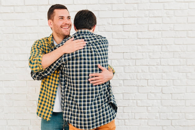 Smiling portrait of a man giving hug to his friend against white brick wall