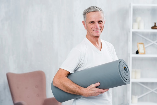 Smiling portrait of a man holding rolled yoga mat at home