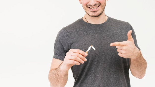 Smiling portrait of a man showing broken cigarette isolated on white background