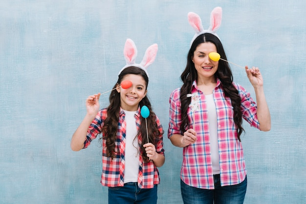 Smiling portrait of a mother and daughter covering one eye with easter egg prop