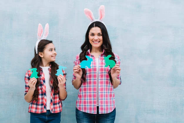 Smiling portrait of mother and daughter holding paper cutout bunny against blue wall