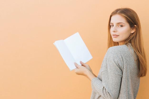 カメラを見て手に本を持って美しい若い女性の肖像画を笑顔